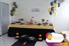 Mesa de bolo decorada com balões e uma pista de carro. Decoração Pam Carvalho festa e eventos. Balões duplos preto e amarelo Qualatex. Balões: www.balaocultura.com.br