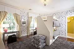 Chic girls' bedroom features walls clad in Schumacher Birds and Butterflies Wallpaper lined with a white bunk beds fitted with a built in staircase dressed in white and black striped bedding placed atop a gray shag rug.