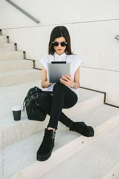 Modern businesswoman sitting at withe stairs working with digital tablet.  by Eduard Bonnin