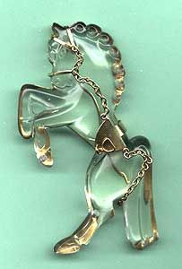 "PRANCING HORSE of Lucite except saddle and reins.  Attached to a gold tone metal frame. Unsigned but marked Sterling, 4"". Circa 1942."