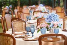 Cadeiras; sousplat; taças bico de jaca (tons azuis para padrinhos/pais/noivos); arranjos baixos com flores tons azuis.