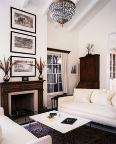 Fireplace Decor Ideas: A wooden mantelpiece helps break up an all-white room. Antique animal etchings stacked above help unite cathedral ceilings with the eye-level living area, while feather-filled urns call out the room's nature theme.
