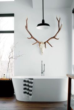 I never suggest a light over the tub but I do like this light in this bathroom, antlers, soaking tub, black gray or white turkish towel