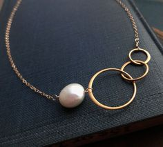 gold karma necklace, Freshwater pearl, bridesmaid gifts, eternity necklace, entwined rings, sisters, best friends, circle necklace. $33.25, via Etsy.