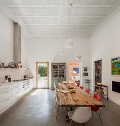 This Barcelona kitchen boasts high white ceilings, white cabinetry, polished concrete flooring and large community style wood table.