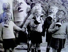 Young children wearing their gas masks.