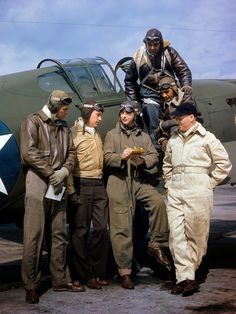 Curtiss Wright's chief test pilot H. Lloyd Child (center) writes on a clipboard as he stands with other pilots on a tarmac near the companies manufacturing plant, Buffalo, New York, 1941.