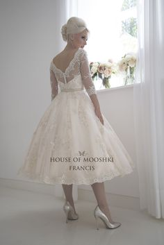 A decadent and opulent vintage tea length wedding dress. Made from our custom champagne lace over champagne satin and heavily embellishment to the lace.  A fully structured bodice overlaid for a bateau illusion neckline and 3/4 length sleeves.  The dress has a modern champagne leather belt to add a modern touch.  www.houseofmooshki.com/our-dresses/francis