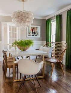 Love this rustic modern dining room. Love the marble and gold dining table, the eames chairs and those pantone greenery drapes