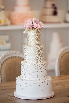 amazing four tier white wedding cake embellished with gold and topped with gorgeous pink flowers -  Indigo Crossing
