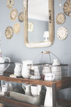 Mirror. Clock faces. Wire baskets. White