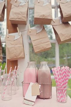 old glass milk containers with chocholate and strawberry milk. perfect for kids and a cute straw to go along with it