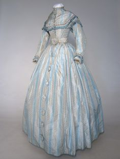 Day dress, ca.1867 [My notes: After 1865, the fashionable waistline was raised somewhat and the elongated back trains of 1864-66 disappeared, to become a sort of loose bustle shape by 1868.  This then was transformed into a more formal, permanent bustle silhouette by 1872-3.]