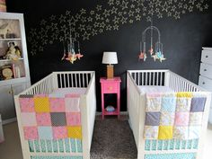 Twin nursery room with chalkboard paint wall and colorful bedding sets