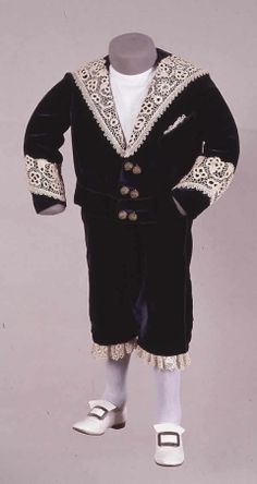 1890 small boy's suit of deep blue velvet, trimmed with Irish crochet lace.