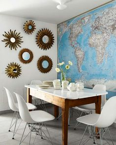 map wall, sunburst mirrors, mid-century chairs, vintage farm house table