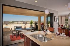 Glass doors open wide to bring the outdoors in. Residence Two by Pulte Homes. The Latitude new home community in San Diego, CA.
