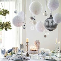 Paper balls over Christmas table - unsure exactly how to hang the ornaments over the table but it looks stunning.