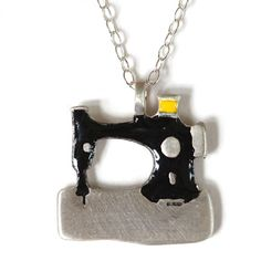Sewing machine charm necklace  We couldn't launch a jewellery collection without including the Singer sewing machine! It makes a very fine charm, we're sure you'll agree, and the perfect gift for a crafty friend. In solid silver with black and yellow enamel details.   Hand crafted in Cornwall by Justin Duance for Poppy Treffry.