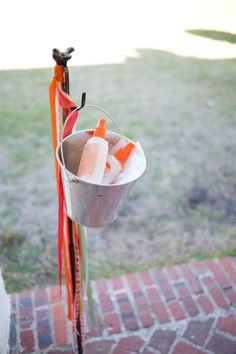 bug spray stand for outdoor parties- just use a short shepherd's hook and bucket.