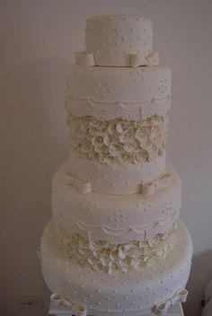 bolo em isopor revestido massa de biscuit branco 7 andares detalhes de laços ,bolinhas renda e flores