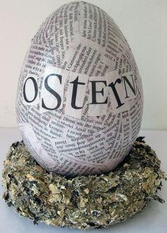 Ei mit Zeitungen als Collage beklebt und einem Text: Ostern    Das Ei steht auf einem kleinem Kränzchen aus Borke - dieser Kranz ist ein Dekoration...