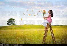 Girl blowing big flower petals.  Illinois