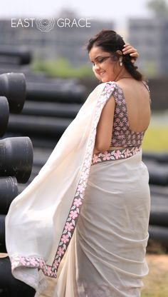 Featuring a misty gray pure georgette saree from EAST & GRACE with beautiful neon pink Frangipani flowers embroidered on the trims and along the pleats of the saree. Pleats are flow-dyed in deeper gray. Send us a message via https://www.facebook.com/eastandgrace. Visit www.eastandgrace.com. Saree on Sale! Price: RS.9,000.