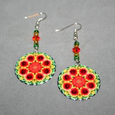 Silver dangle earrings with a Gaillardia (blanket flower) mandala sacred geometry charm titled A Ray of Hope. <br /> <br />These lightweight, dainty silver earrings begin with a dangle of green and yellow Czech glass beads and auburn Swarovski crystal beads that accentuate the colors in the mandala charm that has scalloped edges that catch the light. The mandal...