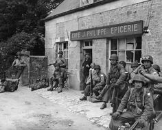June, 20 1944: American soldiers rest in front of a rural grocery store after advancing inland from their D-Day invasion of Normandy, France,. A French citizen smiles from the doorway. The soldiers wears their helmets and uniforms, holding rifles.