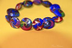Ausgefallenes Armband bestehend aus 13 handgefertigten Linsen aus Polymer Clay.    Die Perlen aus Polymer Clay (Fimo) sind von Hand geformt, gebohrt,