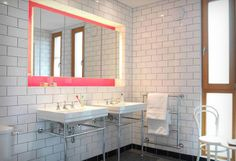 Light source hidden behind a floating mirror positioned in a recessed niche painted a flattering shade of pink.