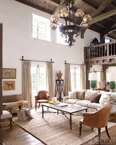 The 19th-century leather chairs in the living room are English, the sofa is by Buckingham, and the settee is upholstered in a Rogers & Goffigon velvet; the small table is made from an apple-tree stump, the curtains are of a cotton from Claremont, and the jute rug is by Pottery Barn.