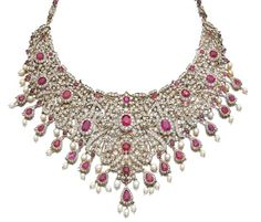 RUBY, CULTURED PEARL, AND DIAMOND NECKLACE. Of bib design, composed of floral and foliate motifs embellished with cushion-shaped and circular-cut rubies and set with circular- and single-cut diamonds, suspending a fringe of pear-shaped rubies, framed with circular- and single-cut diamonds, and cultured pearls, length approximately 370mm.