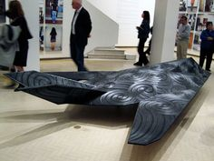 Brett Graham: Weapons of mass destruction. Stealth bomber with its identity reformed by carved Maori designs.