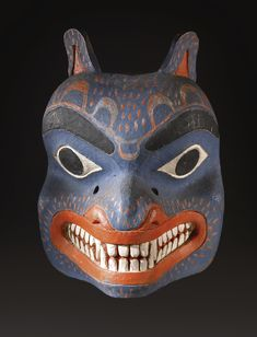 NORTHWEST COAST POLYCHROME WOOD MASK, PROBABLY BELLA COOLA    of deeply hollowed form, depicting a bear, wearing a voracious expression, carved with thick lips pulled back to reveal jagged teeth, flaring nostrils, and exaggerated pointed oval eye rims beneath arched brows, painted overall with a series of dashes; the back with a wooden structure for attachments and use.  height 19 1/2 in.