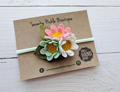 This triple cluster headband made with wool felt. The headband includes three hand cut daisies with gold felt centers and green leaves. The flowers are attached to a stretchy mint nylon headband. Nylon Headbands are one size fits most and are perfect for babies and toddlers.