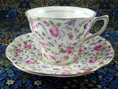 This is a Rosina, England cup and saucer with a design of a pink roses and purple violets chintz design on white bone china with gold trim in pattern number 5044 from the 1950s. The cup measures 2.5 i
