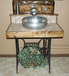 """Our """"New"""" Washstand...sewing machine base, cream separator sink, old coffee pot spout and a sugar bowl faucet handle...how cool is that!!"""