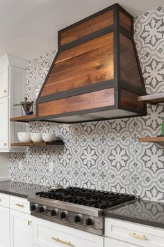 A stunning stained oak hood is complemented with floating wooden shelves fixed to Cement Tile Shop Bordeaux III backsplash tiles and located above white shaker cabinets accented with brass hardware and a charcoal gray quartz countertop fitted with a stainless steel cooktop.