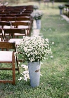 ivory rose petals lightly sprinkled on the sides of the aisle, with galvanized tins filled with white waxflowers and seeded eucalyptus.