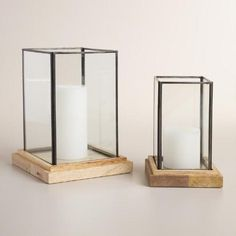 Glass panes in a welded metal frame contrast modern design with an antique-burn finished wooden base. Fill with a glowing candle and set out large and small for a contemporary lighting update.
