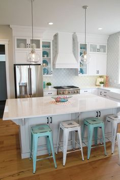 Oh how I love this kitchen! White on white with colorful accents and check out those stools!