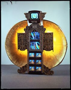 "Nam June Paik, ""Zenith,"" 1992. Courtesy Carl Solway Gallery, Cincinnati. One antique Zenith TV cabinet, painted & carved wood cabinets, 2 satellite dish sections with gold leaf, six 10"" televisions, two 19"" color televisions, one 13"" color television, lightbulbs, antenna, 3 DVD players, 3 channel original Paik video on 3 DVDs."