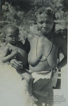 Portret van een bosneger vrouw met kind op de arm. Let op de scarificaties (kamemba) op borst en buik, en in het gezicht. Datum: okt 1959 Locatie: Suriname Vervaardiger: frater Solanus Essed