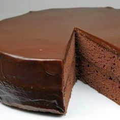 Flourless Chocolate Cake with Chocolate Glaze | This moist and dense chocolate cake is topped with a smooth, rich dark chocolate ganache that melts in your mouth. Serve it with sweetened whipped cream and raspberries for a delightful and elegant desert.