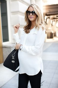 Pregnancy fashion. White blouse, black jeans.
