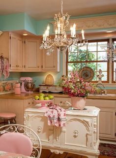 Shabby Chic look. This gorgeous vintage white French island adds to elegant and chic feelings to this cream and pastel color themed kitchen. It is really fitting everything, the lovely ornate elements painted over in a soft cream, a chandelier hangs from the ceiling, and retro kitchen aid appliances in pink enamel and so on.