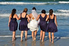 Bridesmaids linking arms on the beach, how sweet! By Clearly In Focus Photography.