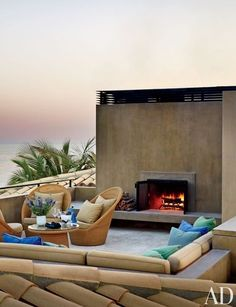 A Mexican rooftop lounge, with a pigmented-concrete fireplace, features a Jardin de Ville table and chairs; the blue and green pillow fabrics are by Perennials | archdigest.com